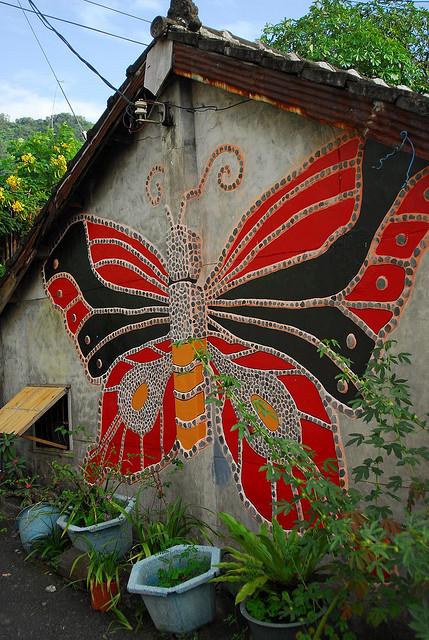 Бабочка из гальки на стене дома